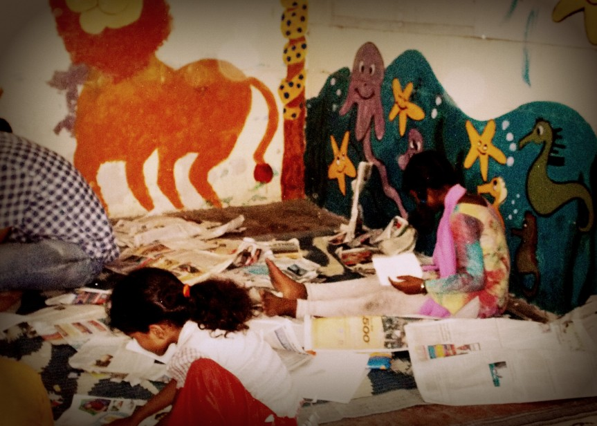 Picture of children doing some crafts using recycled newspaper. The colourful paintings on the walls were done by the volunteers and the children of the shelter.