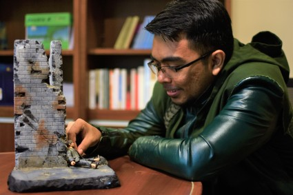 Ihsan with a diorama he designed and made by hand