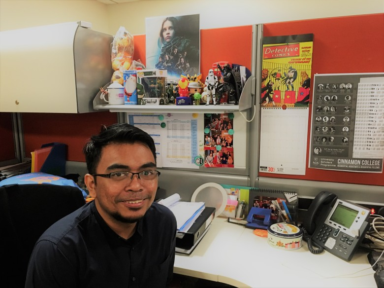 Ihsan sitting in his office cubicle